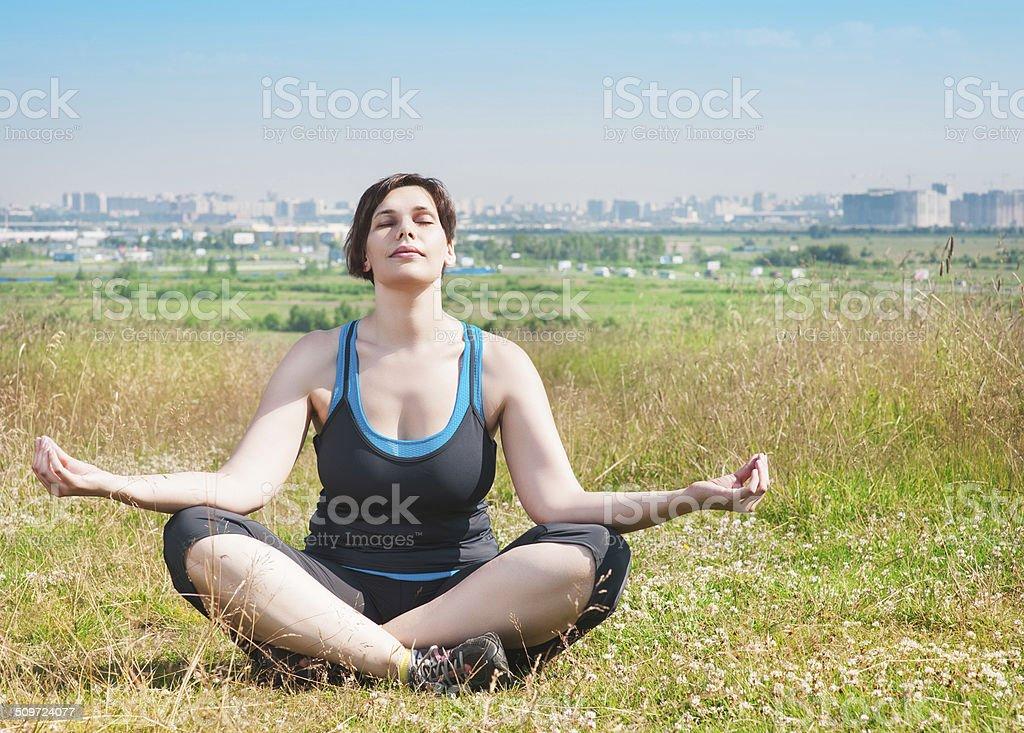 Beautiful plus size woman doing yoga stock photo