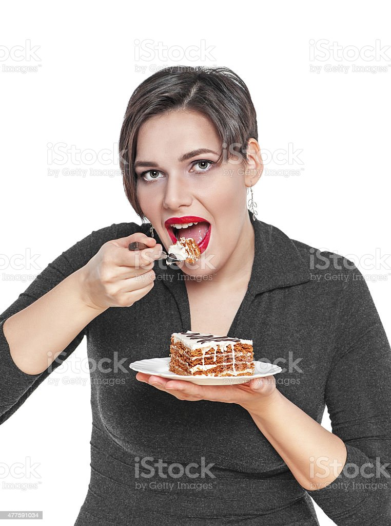Beautiful plus size woman eating cake isolated stock photo