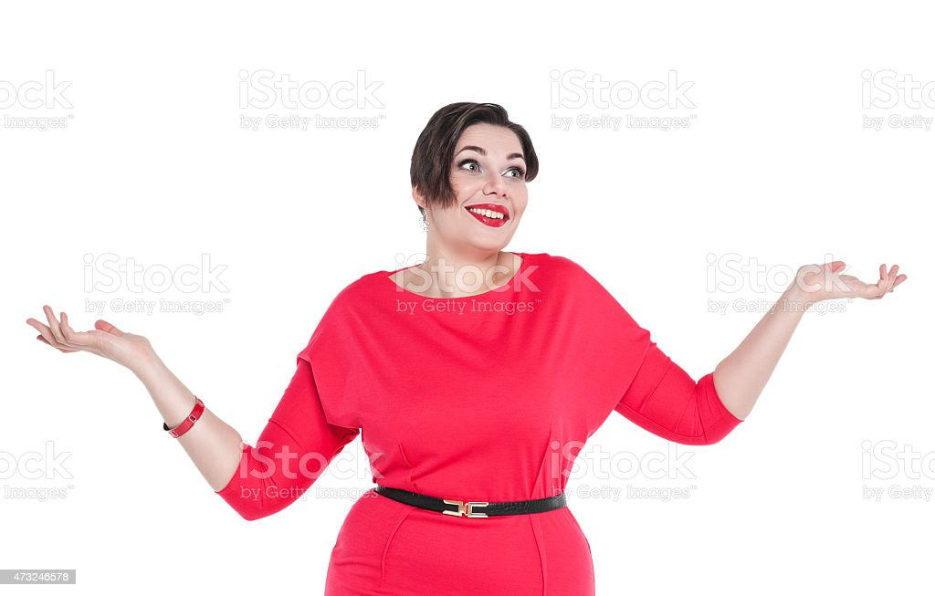 Beautiful plus size woman in red dress shrugs her shoulders stock photo