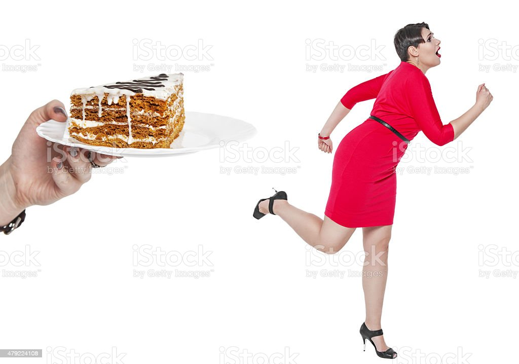Beautiful plus size woman run away from cake isolated stock photo