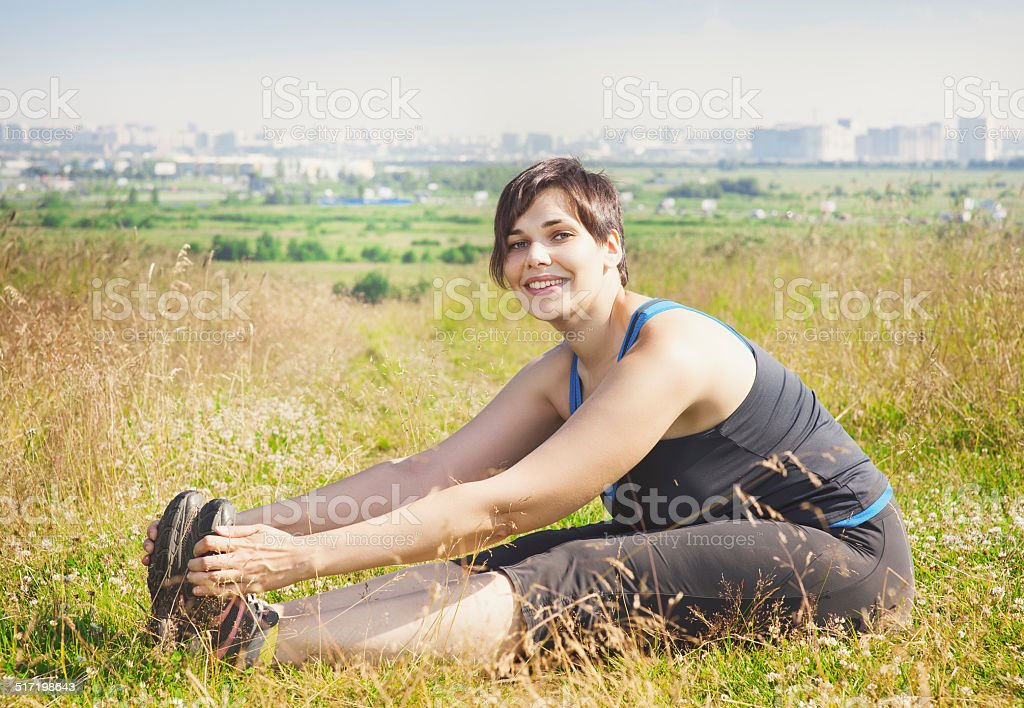 Beautiful plus size woman stretching outdoor stock photo