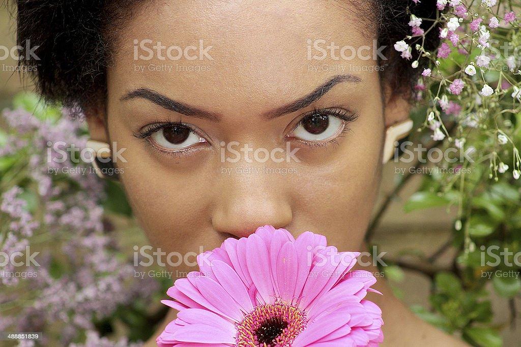 Bellissimo Ritratto di una giovane donna che tiene un fiore di colore rosa foto stock royalty-free