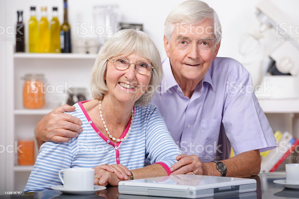 Beautiful Portrait Of Senior Couple  In A Domestic Kitchen royalty-free stock photo
