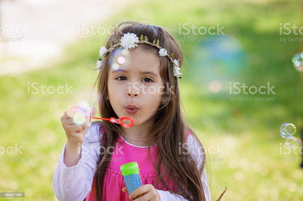 Beautiful portrait of sweet lovely little girl blowing soap bubb stock photo