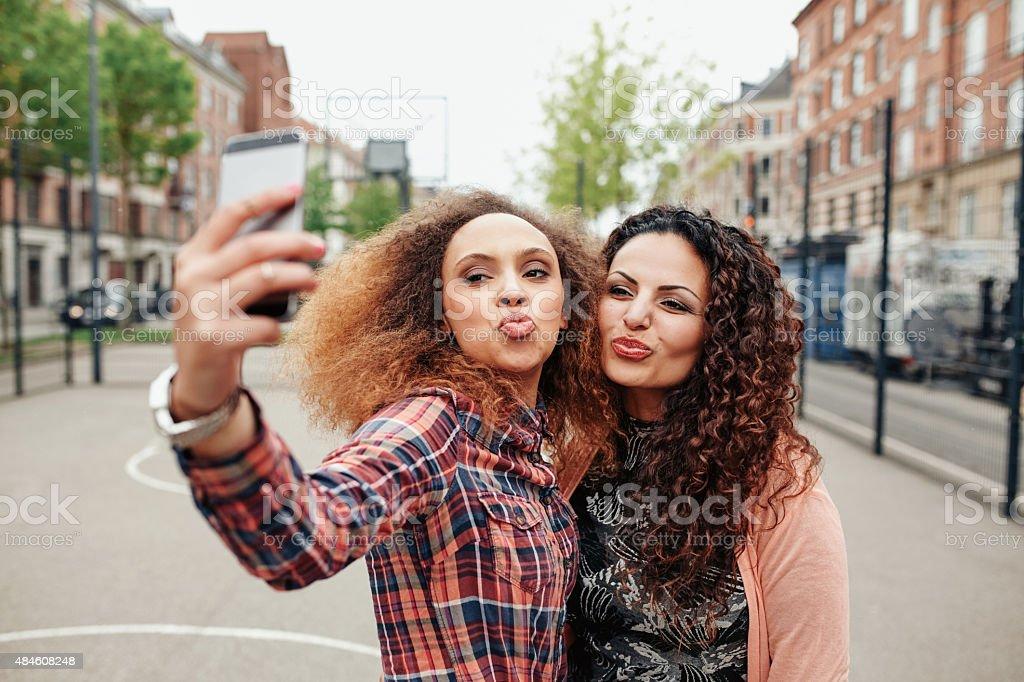 Beautiful pouting women taking a selfie stock photo