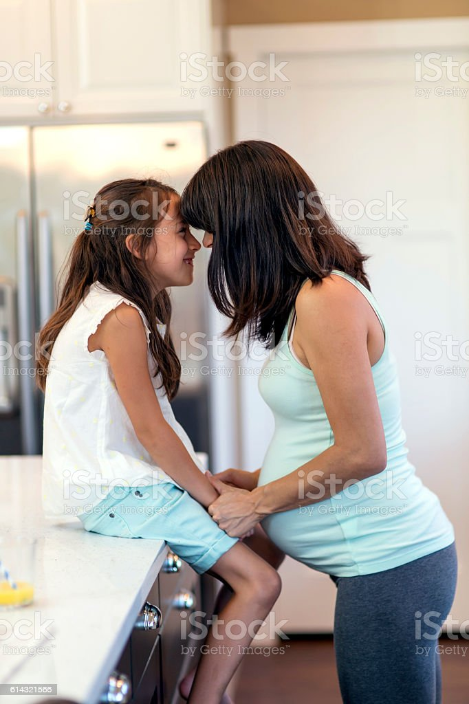 Beautiful pregnant mother and daughter touch foreheads together stock photo
