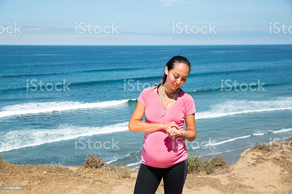 Beautiful pregnant woman checking her heart rate stock photo