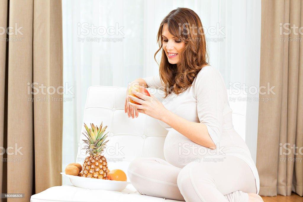 Beautiful pregnant woman eating fruit royalty-free stock photo