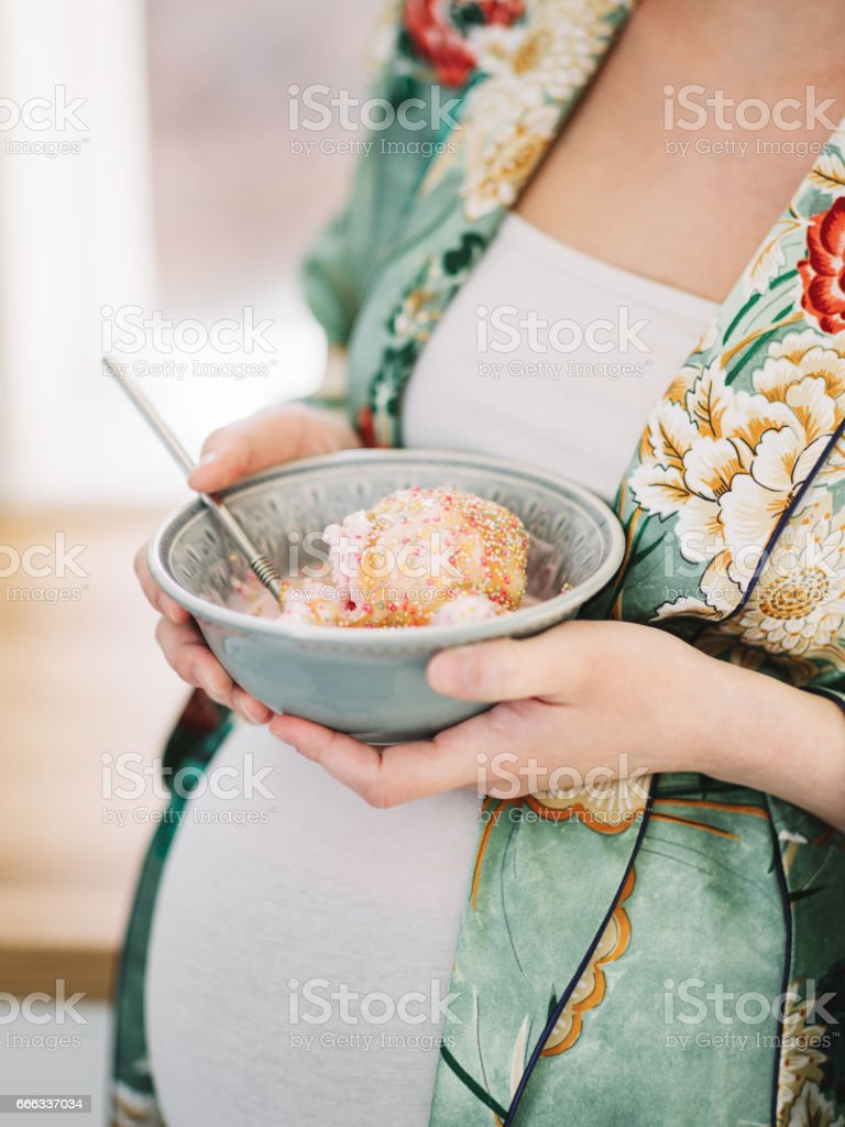 Beautiful pregnant woman eating ice cream stock photo