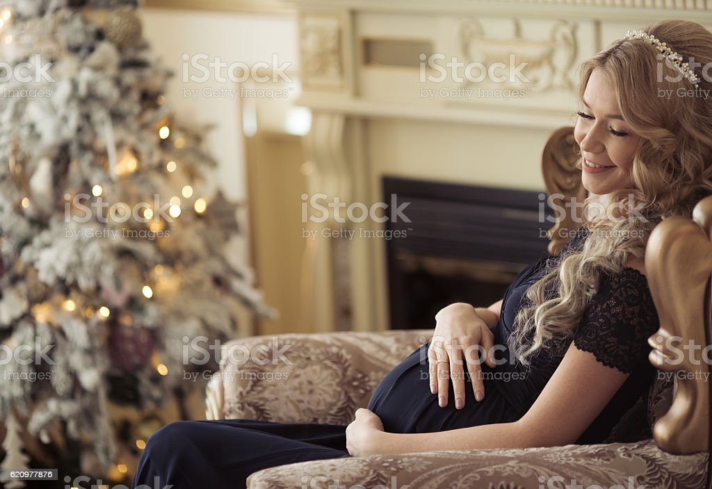 Beautiful Pregnant Woman In A Holiday Dress. Christmas Tree Background. stock photo