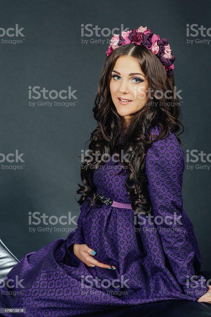 beautiful pregnant woman in a purple dress stock photo
