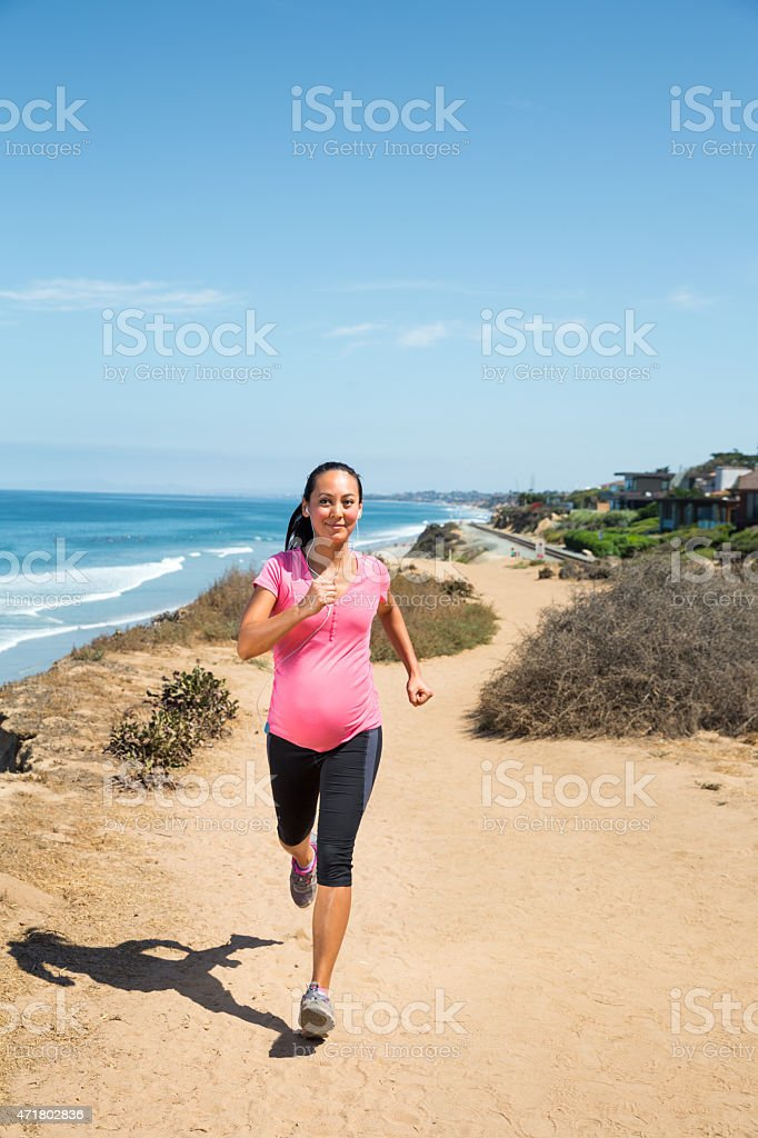 Beautiful pregnant woman jogging along the coast to stay fit stock photo