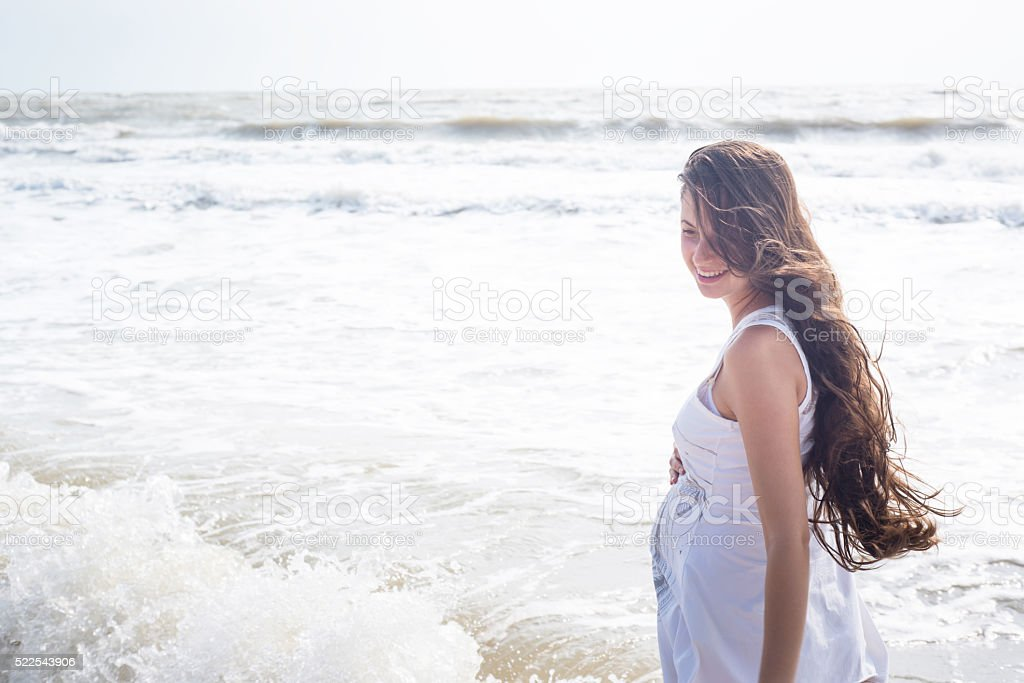 Beautiful pregnant woman smiling on the sea shore stock photo