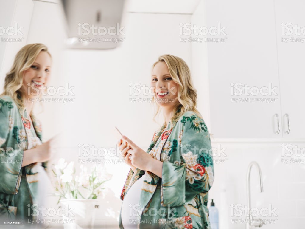 Beautiful pregnant woman with smart phone in the kitchen stock photo