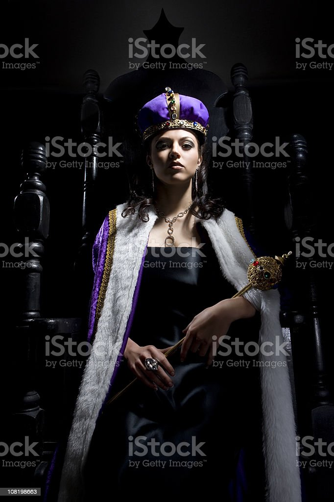 Black Throne with Beautiful Queen Holding Scepter stock photo