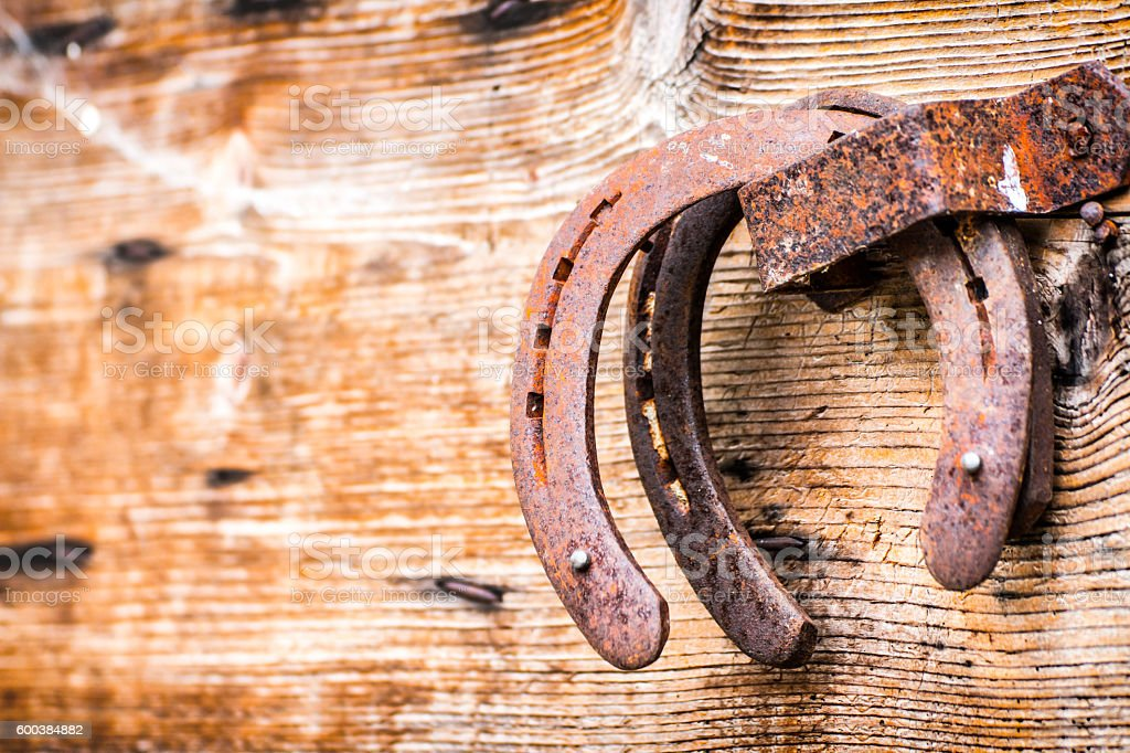 Beautiful real old horseshoe hanging from an aged wooden door stock photo