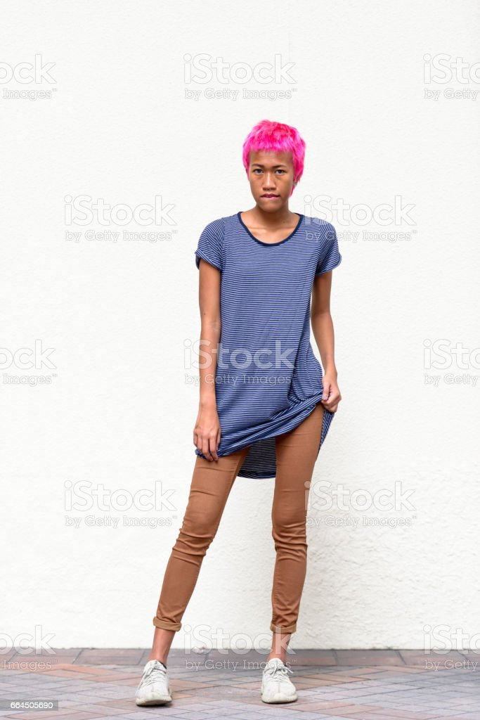 Beautiful rebellious young woman with short pink hairstyle biting her lip stock photo