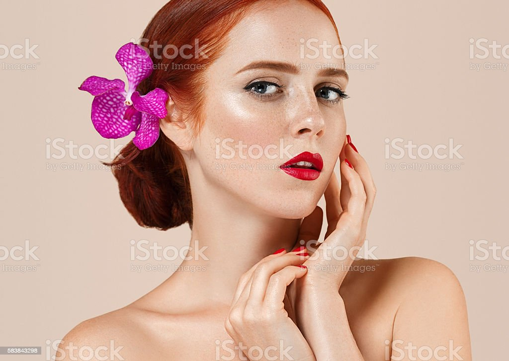 Beautiful red hair woman with flower. Perfect make up manicure stock photo