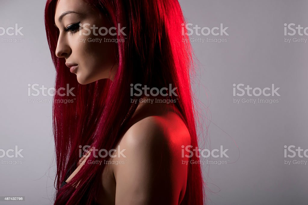 Beautiful red haired woman posing over grey background stock photo