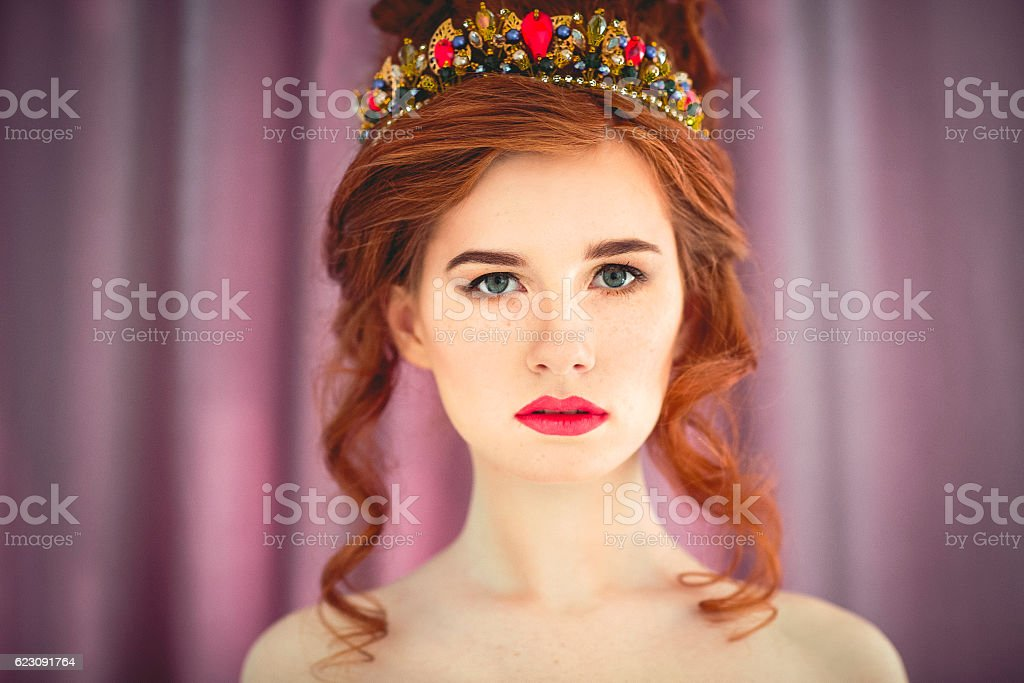 Beautiful redhaired fashion model posing in evening dress stock photo