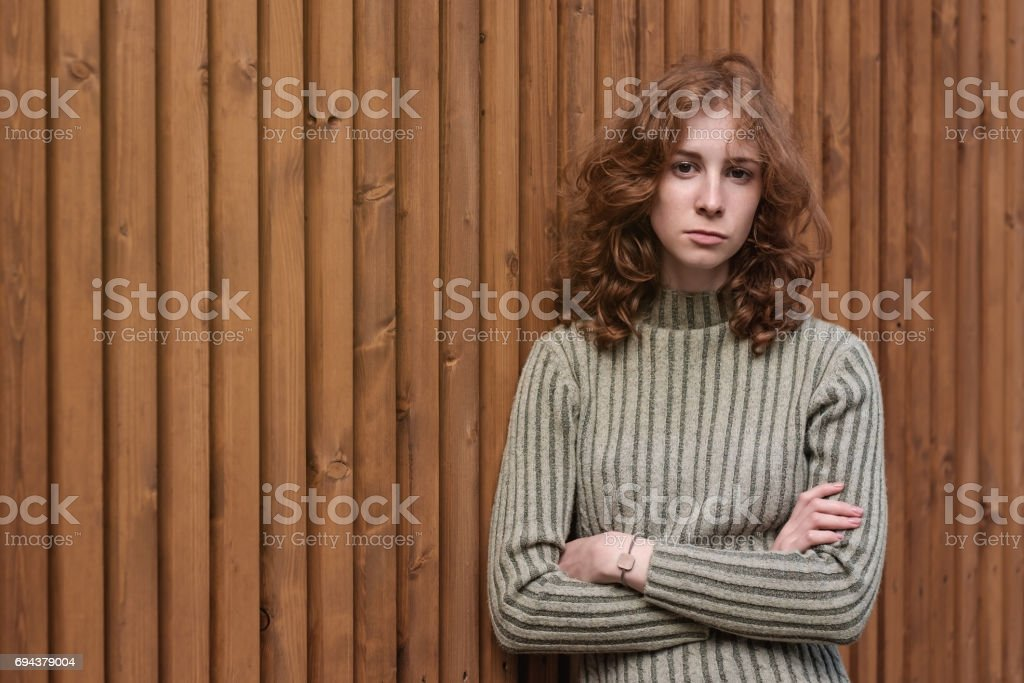 A beautiful red-haired girl in a green sweater is standing by the wooden wall. stock photo