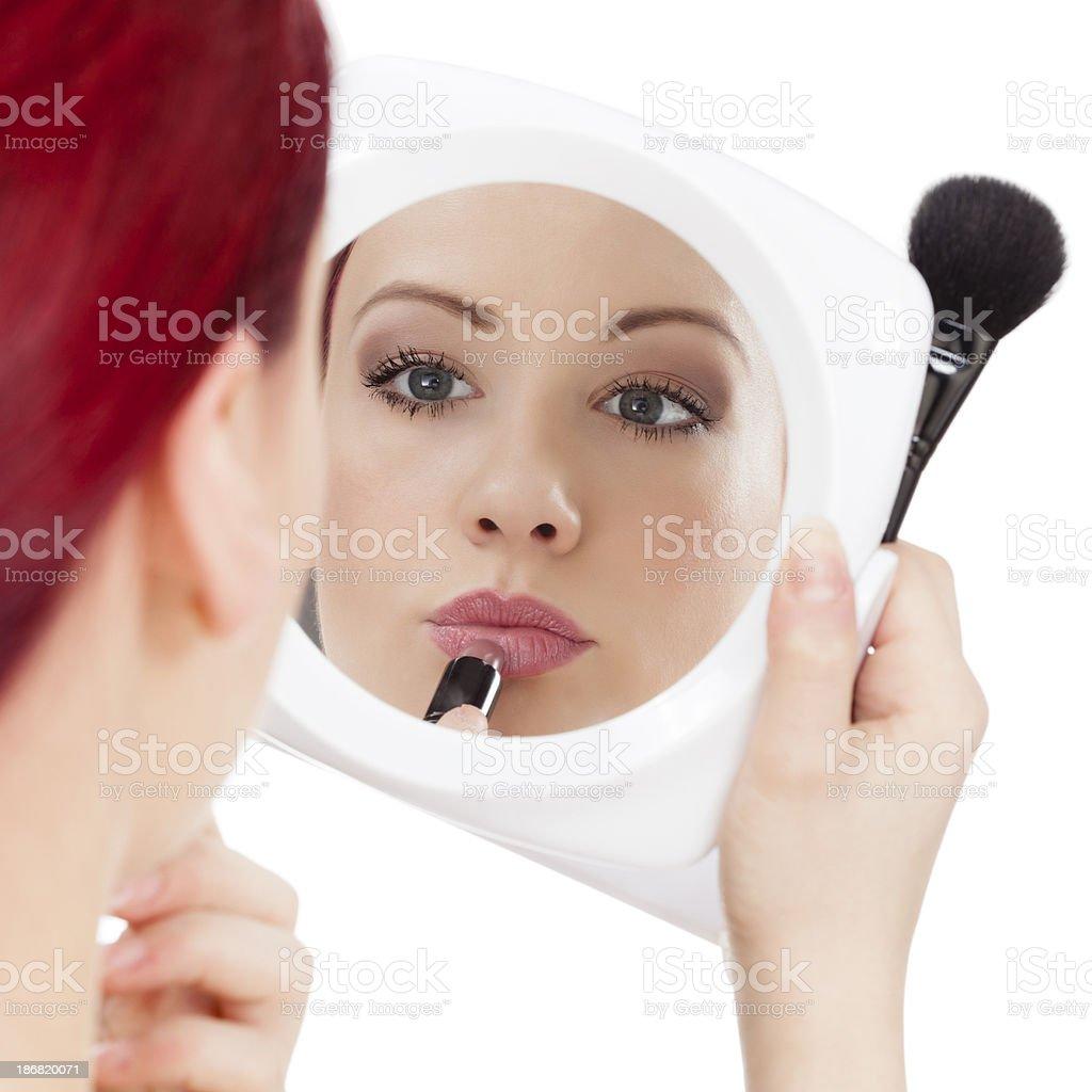 Beautiful redhead girl applying make up royalty-free stock photo