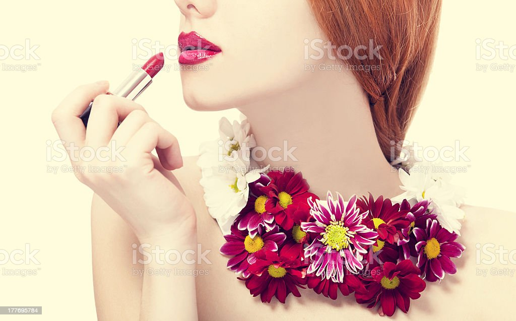 Beautiful redhead girl with flowers holding lipstick royalty-free stock photo