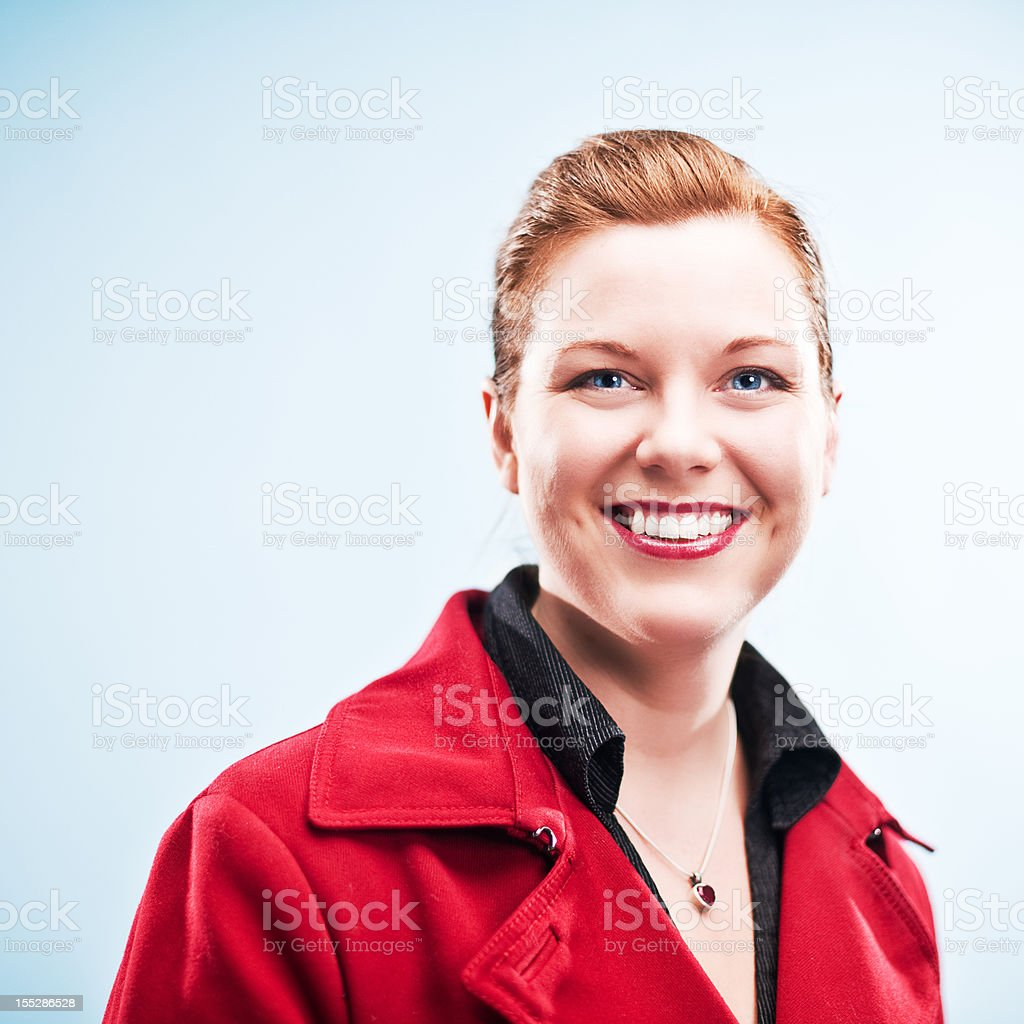 Beautiful redhead in red coat royalty-free stock photo