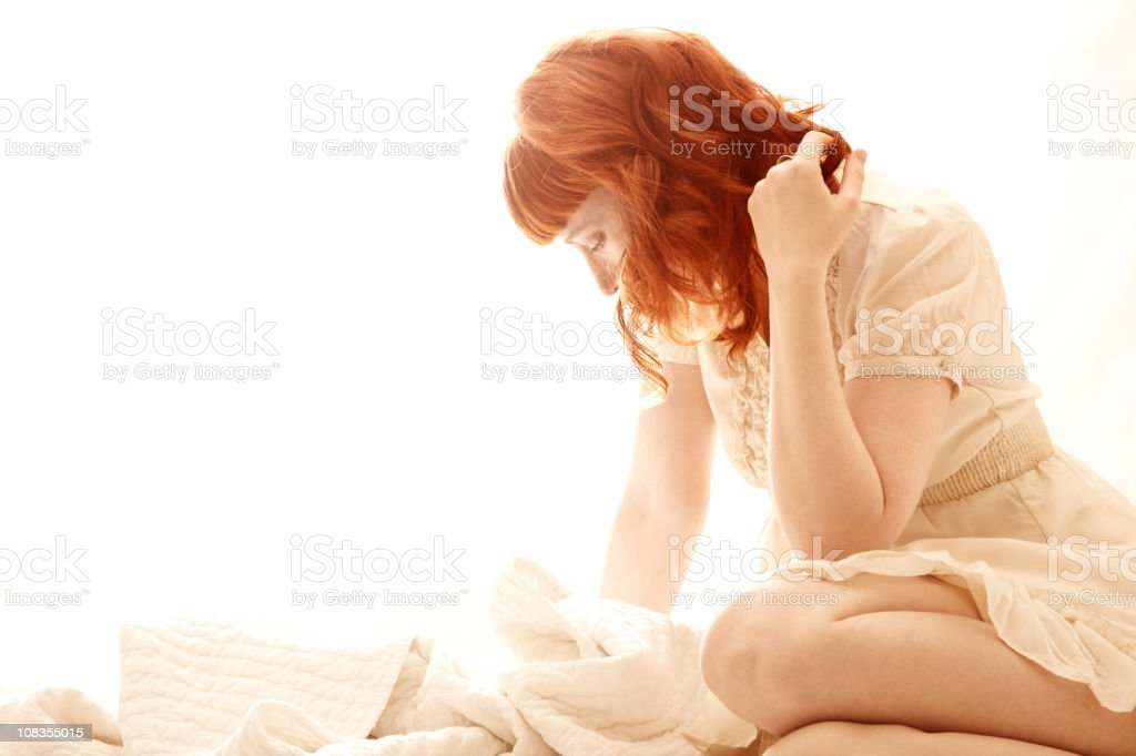 Beautiful redhead sitting in bed looking down royalty-free stock photo