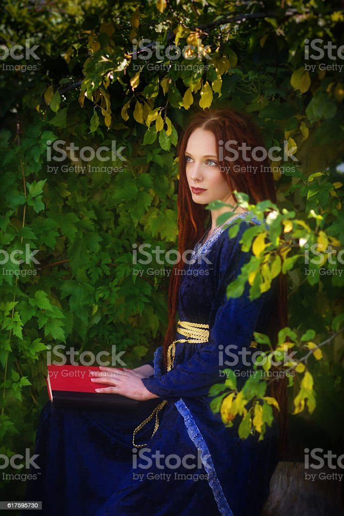 Beautiful redhead sitting with book in lap looking away. stock photo