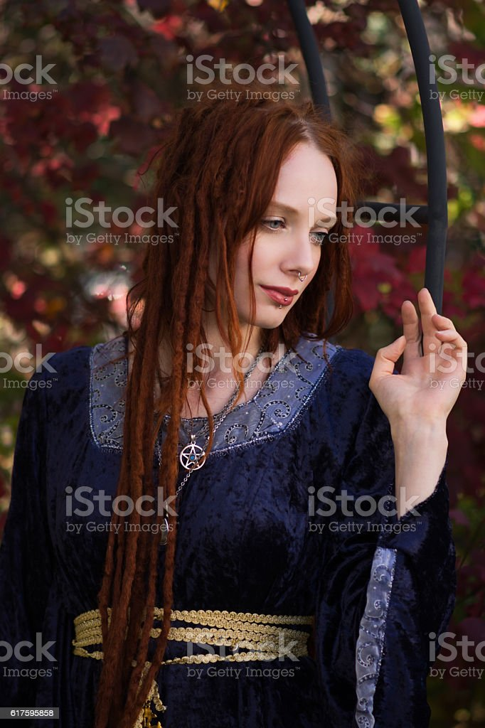 Beautiful redhead with soft smile in autumn garden, waist up. stock photo