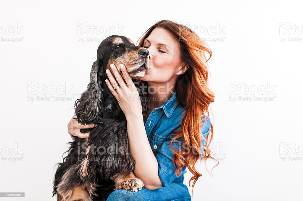 Beautiful redhead woman on her 40s with her dog stock photo