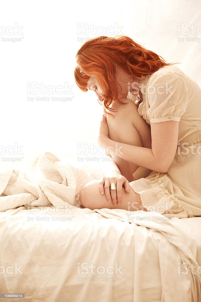 Beautiful redhead woman sitting in bed royalty-free stock photo