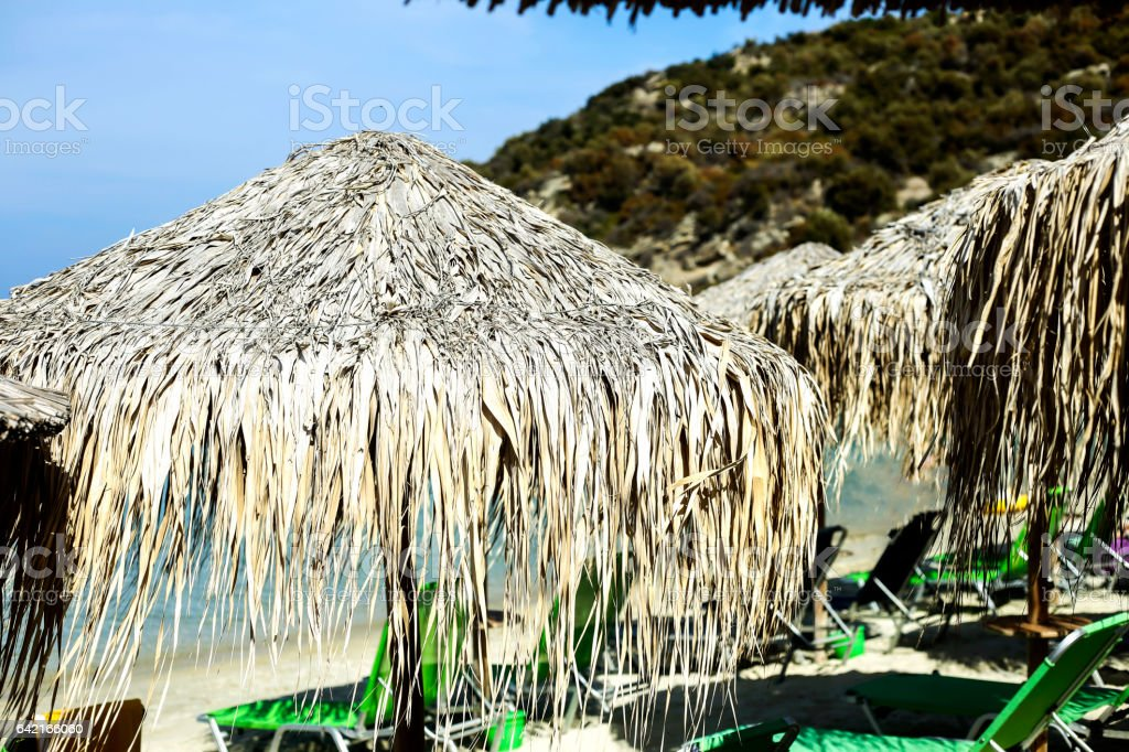 Beautiful reed parasol and beach chairs stock photo