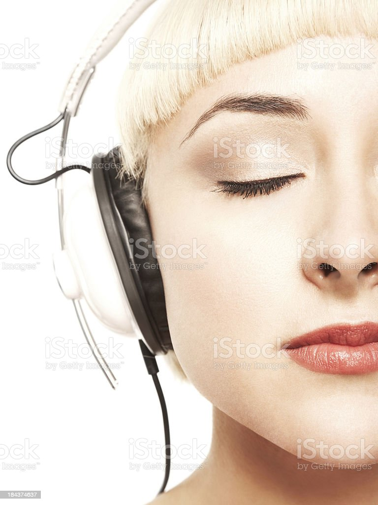 Beautiful relaxed blonde young woman enjoying music with headphones royalty-free stock photo