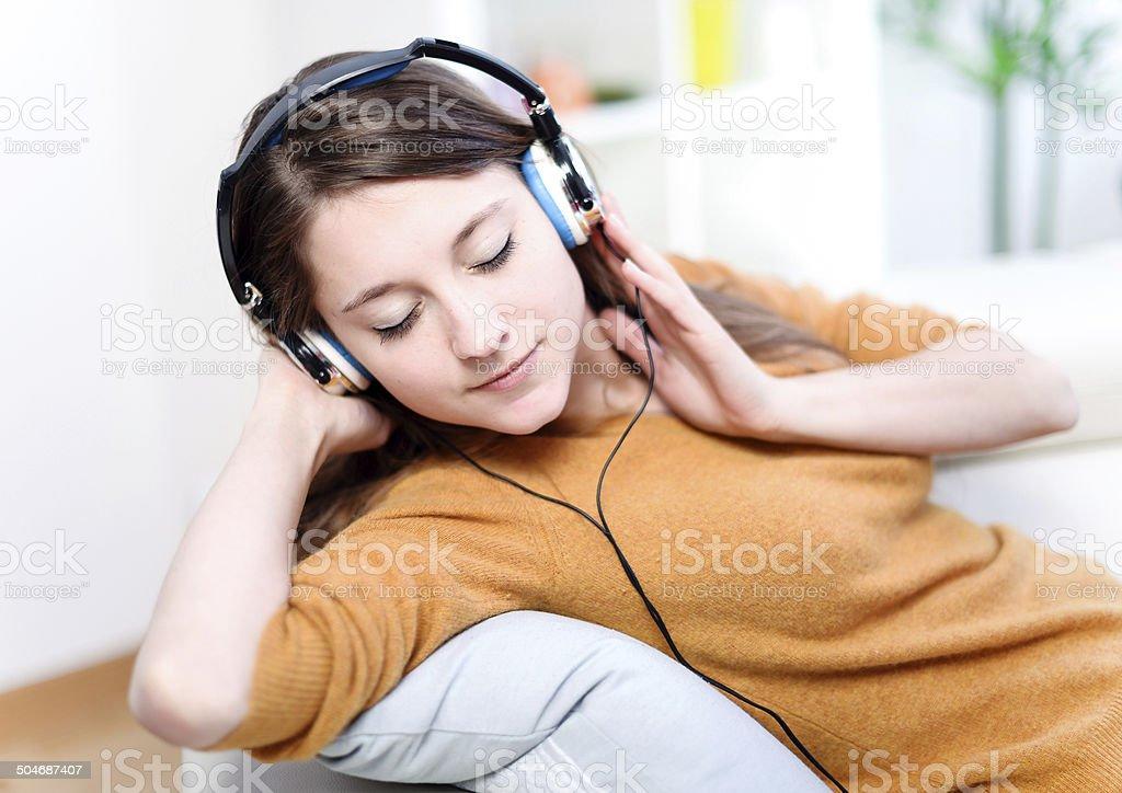 Beautiful relaxed young woman listeningto music stock photo