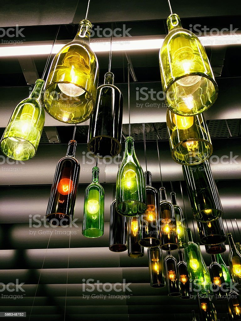 Beautiful retro light lamp decor made of the wine bottles stock photo