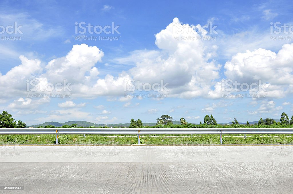 Beautiful roadside view with green nature and cloudy blue sky stock photo