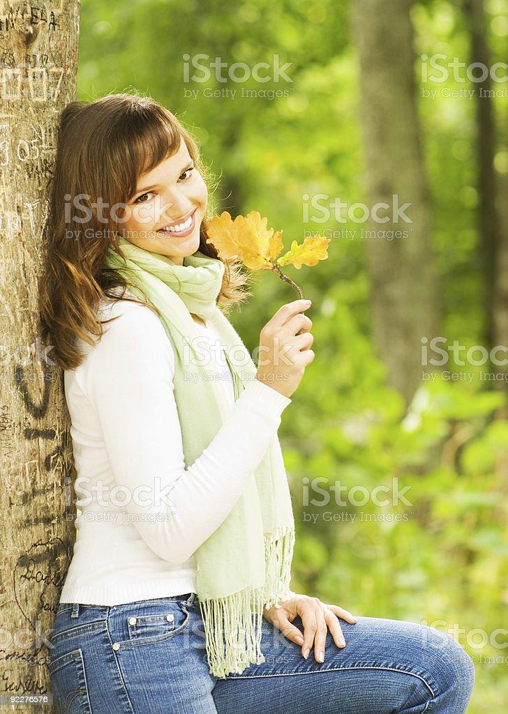 Beautiful romantic brunette with golden autumn leaf close-up por royalty-free stock photo