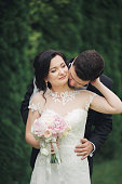 Beautiful romantic wedding couple of newlyweds hugging in park on