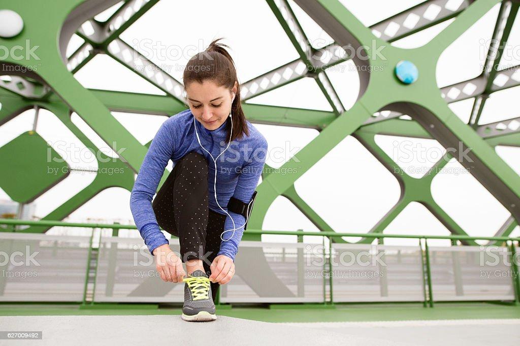 Beautiful runner in the city tying shoelaces on steel bridge stock photo