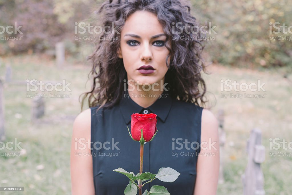 Beautiful sad girl holding red rose on old cemetery stock photo