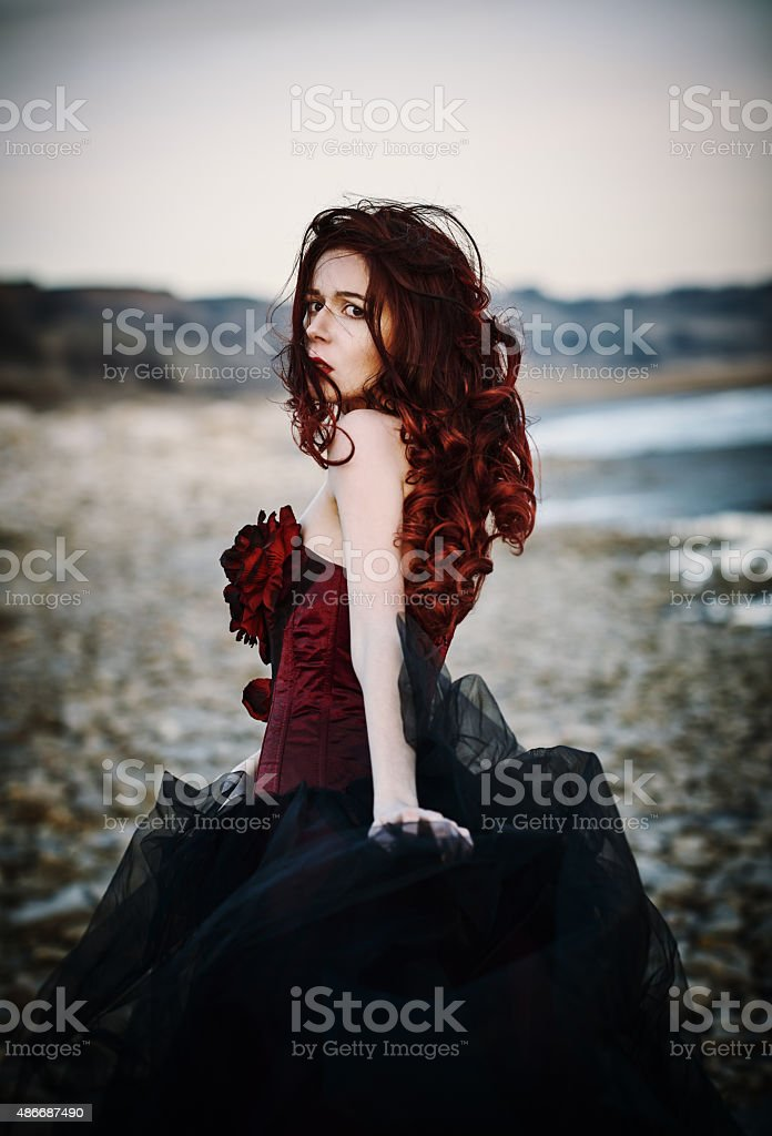 Beautiful sad goth girl standing on sea shore. Rear view stock photo