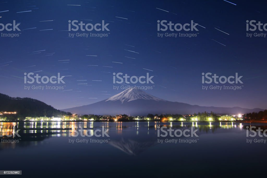 Beautiful scenery of the startrail on night sky at Mountain Fuji in kawaguchiko lake of Japan.This is a very popular for photographers and tourists. Travel and natural Concept stock photo