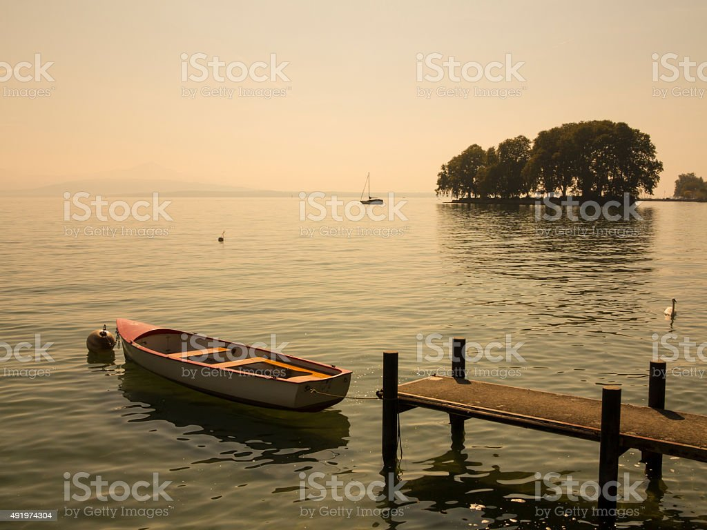 Beautiful scenic view of small island, boat and pier stock photo