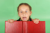 Beautiful school girl peeping from behind her red book