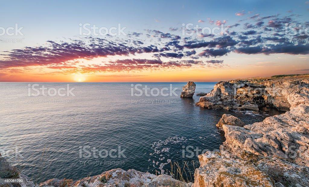 Beautiful seascape. Sea and rock at the sunrise. Nature composition. stock photo