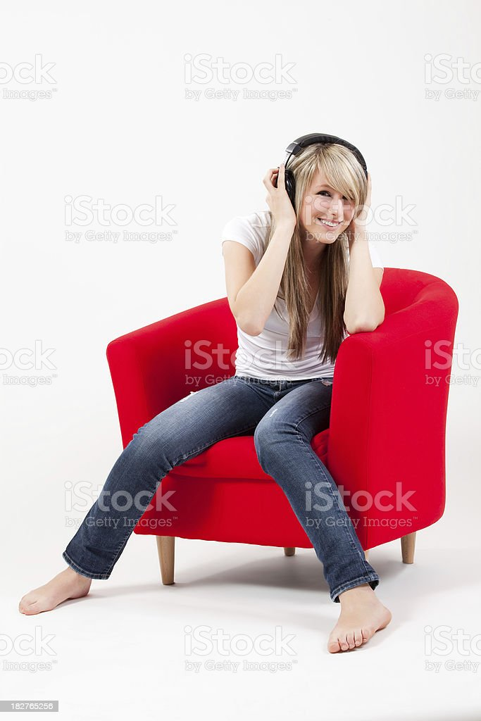 Beautiful, seated girl with headphones listens to music in chair royalty-free stock photo