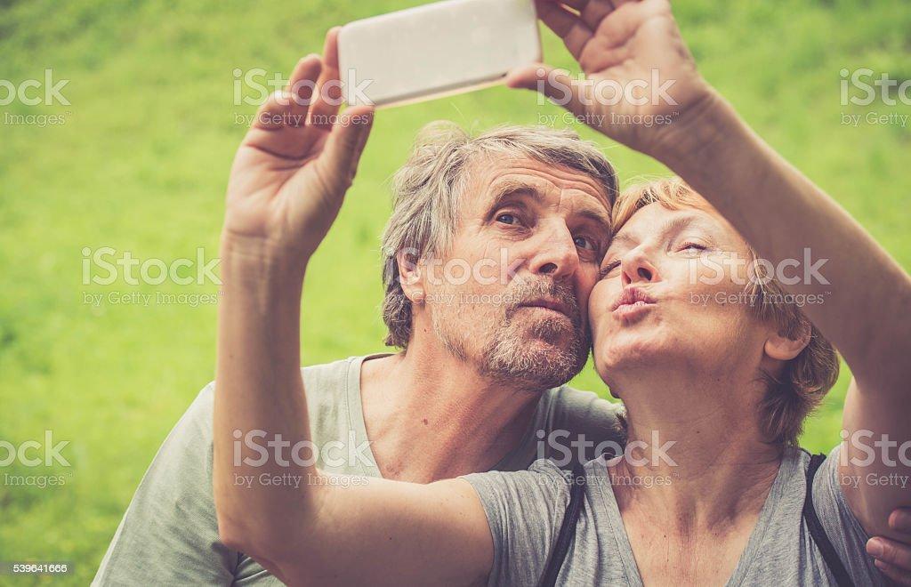 Beautiful senior caucasian couple taking selfie - duck face stock photo