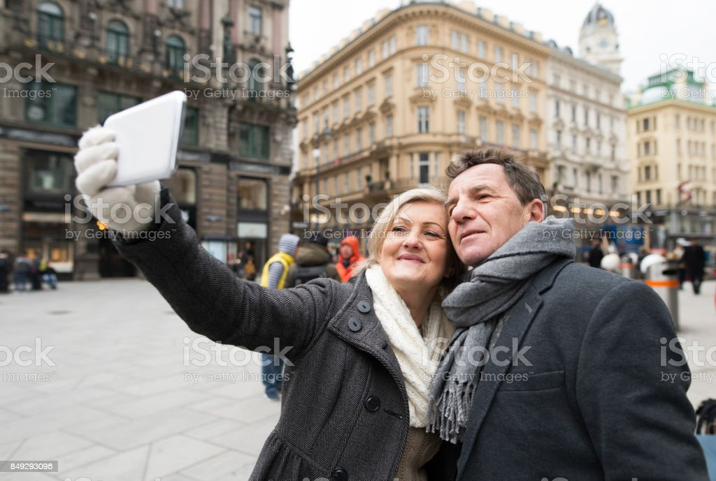 Beautiful senior couple on a walk in city centre taking selfie. stock photo